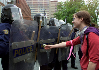 PROTESTOR OFFERS FLOWER TO POLICE LINE OUTSIDE G7 MEETINGS.