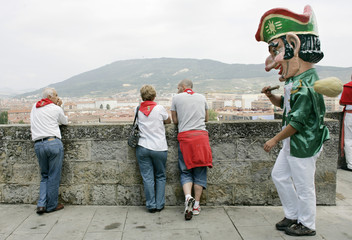 "A ""Kiliki"" prepares to hit a man with a sponge tied to a wooden club in Pamplona"