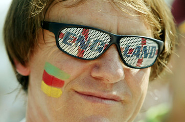 England soccer fan with Portuguese flag painted in the face at a FunPark to Nations Park site in Lis..
