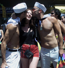 Two Israeli parade-goers wearing sailor hats in Tel Aviv's gay pride parade surprise another partici..