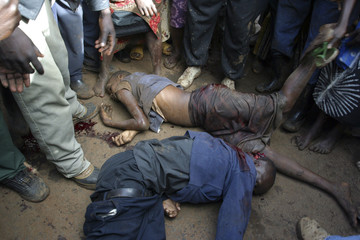 People gather around the bodies of two teenagers killed during opposition protests in Nairobi