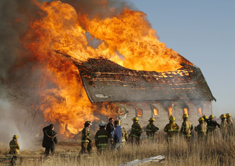 Fire fighters watch an old barn burn after lighting the old prairie landmark on fire for a training exercise near Chestermere.