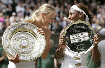 SHARAPOVA OF RUSSIA AND WILLIAMS OF THE U.S. HOLD THEIR TROPHIES AFTER THEIR FINAL AT WIMBLEDON.