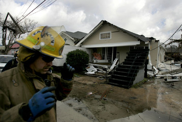 A New Orleans firefighter walks towards a collapsed home after a possible tornado knocked the home off its foundation in the Carrollton area of New Orleans