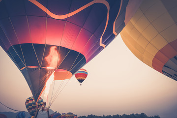 Close-up of Hot Air Balloons with fire at sunset applying retro and vintage filter effect styles.