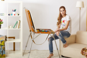 Painter female with wooden sketchbook sitting on sofa and painting