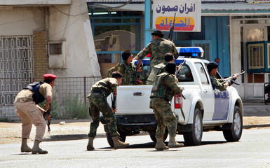 Iraqi soldiers take cover after being fired upon while on patrol in Baghdad.