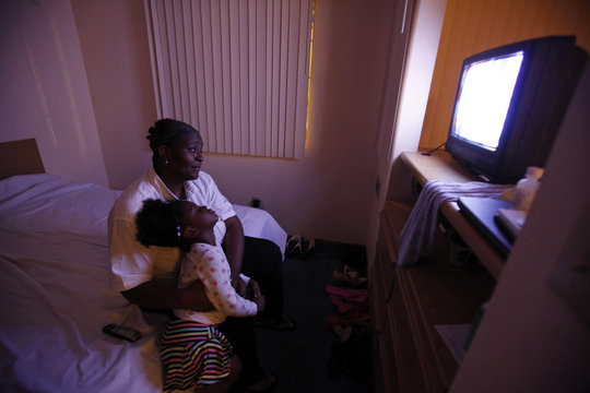 Wilson watches television with her daughter, Woods in the motel room where the family is living in Grand Prairie