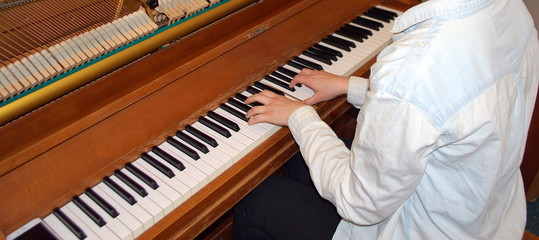 Female piano player performing in concert indoors.