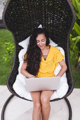 Young successful woman works as freelancer online in outdoor garden. Brunette in yellow dress with silver laptop. Internet work in travel