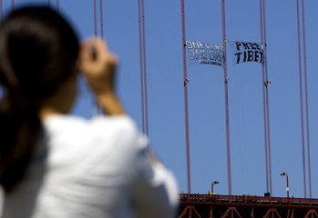 A woman takes a picture of the Golden Gate Bridge as Tibet activists put up banners in San Francisc