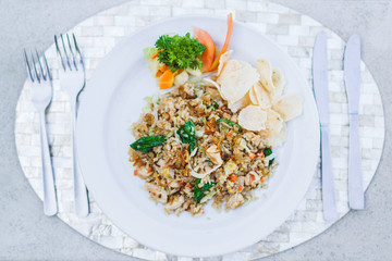 Traditional indonesian nasi goreng with chips, fresh tomato and greens on white plate and silver cutlery on tray