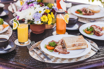American breakfast with fried sausages, tomato, bacon, toasts and greens close up. Fat and unhealthy food.  Table with different meals and fresh juices