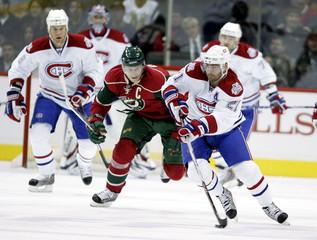 Canadiens Higgins skates ahead of Wilds Koivu during NHL hockey game in St. Paul