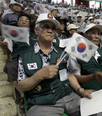 Korean War veterans wave South Korean national flags during a ceremony marking the 58th anniversary of outbreak of the 1950-53 Korean War in Seoul