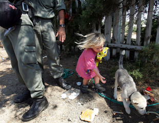 A Jewish settler girl plays with a dog in front of Israeli police in Palm Beach Hotel in Gush Katif ...