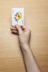 woman hand hold a card on the wood table.