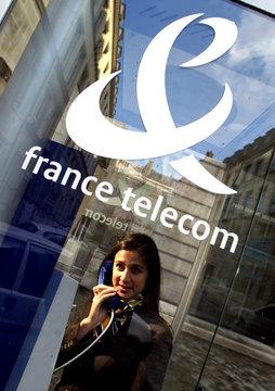 A WOMAN PHONES UNDER FRANCE TELECOM COMPANY LOGO.