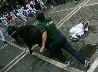 A fallen runner tries to stay away from the bulls during the running of the bulls in Pamplona