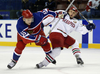 RUSSIAN GONCHAR AND RASOLKO OF BELARUS COLLIDE IN OLYMPIC MENS ICEHOCKEY.