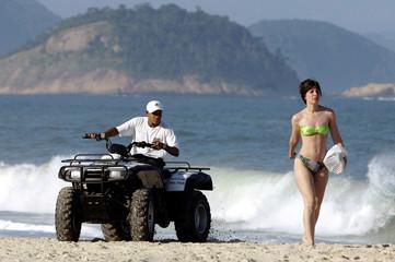 BRAZILIAN POLICEMAN PATROLS RIO BEACH.
