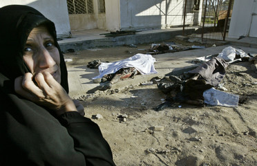IRAQI WOMAN STANDS NEXT TO BODIES OUTSIDE CITY MORGUE FOLLOWING SUICIDE BOMB ATTACK IN ISKANDARIYA.