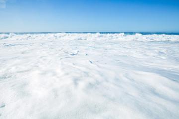 White shorebreak foam upcoming to a shore. Seascape with bright background