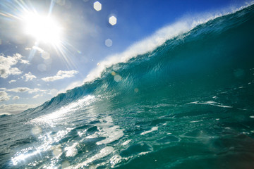 Bright ocean wave barrel ready to close with sun on background