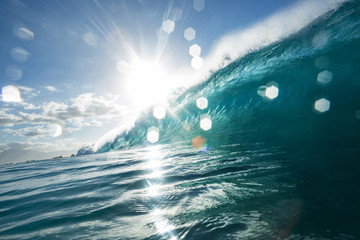 Surfing wave with bright sun and light bokeh on water drops