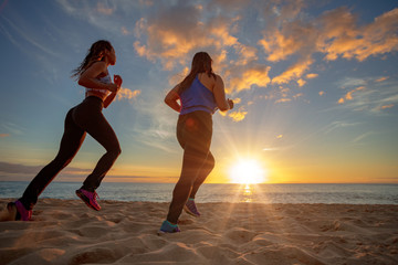 Running girls jogging at beachside at sunset time. Motion blurred image