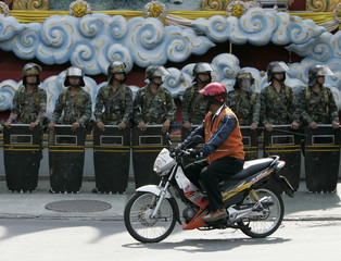 A motorcyclist ride past a line of Thai soldiers standing guards at a street corner near parliament in Bangkok