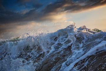 Shorebreak wave crushing with water drops at sunset time