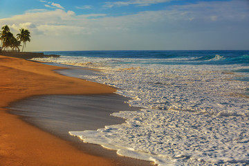 Sea view in morning light. Ocean shore with yellow sand and blue waves. White rough foam on tropical beach