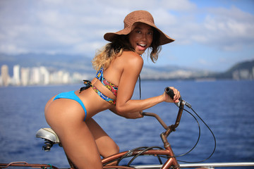 Smiling pacific islander girl weraing bikini sitting on a bike riding bicycle. Seascape with buildings on a beachside.