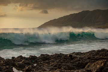 Beautiful green rough ocean wave incoming. Sunset sea with shorebreak water surface. Rocky coastline with mountain landscape on background