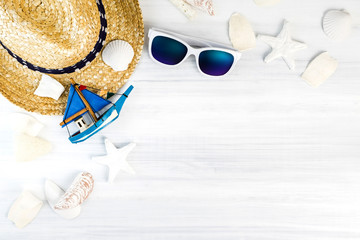 Wall Mural - Summer Beach accessories (White sunglasses,starfish,straw hat,shell) on white plaster wood table top view,Summer vacation concept,Leave space for adding text