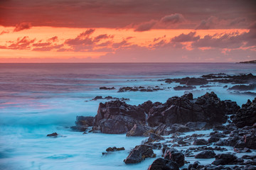 Beautiful red orange sunset in Pacific ocean. White splashes of ocean waves breaking against rocky coast.