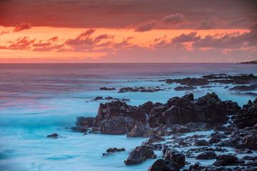 Beautiful red orange sunset in Pacific ocean. White splashes of ocean waves breaking against rocky coast.