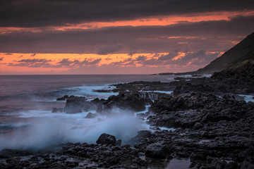 Beautiful sunset in ocean view with pinky orange sky on background. Rocky coastline with splashing against black lava rocks waves