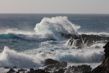 Black rocky shore in Pacific ocean with blue beautiful crushing breaking waves