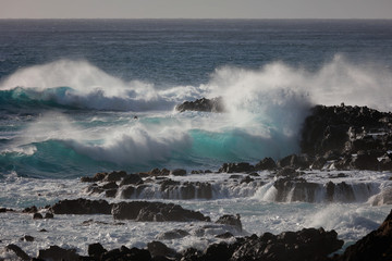 Black rocky coast in Pacific ocean with blue beautiful splashing waves