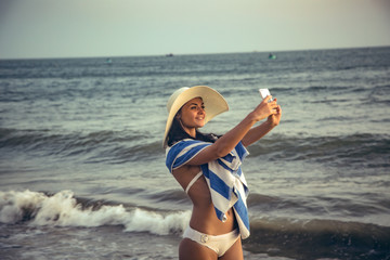 Beautiful girl wearing white hat and hotel towel making selfie on a beach by the sea