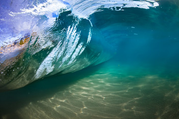 Underwater view of sea water surface in shape of rolling wave with sandy bottom
