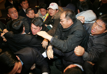 Security personnel and protesters scuffle during a public hearing on bilateral FTA talks in Seoul