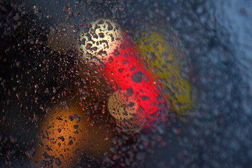 Raindrops over window glass closeup. blurred night background with coloured lights.