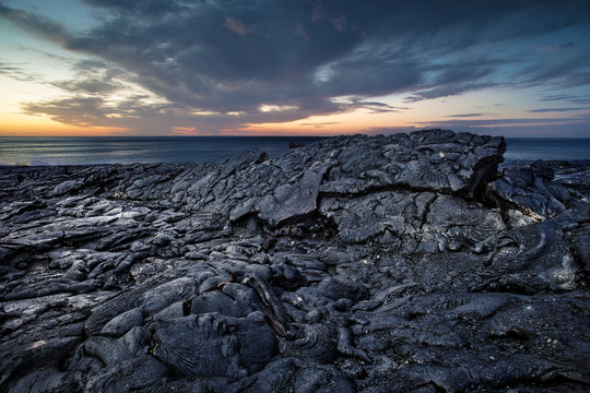 Black scenery of Lava fields, lava rock against sunset ocean at Hawaii