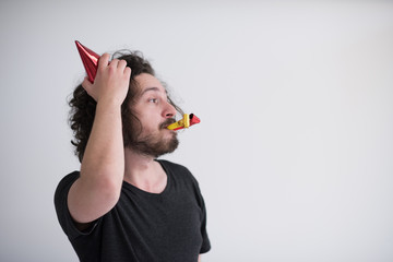 Portrait of a man in party hat blowing in whistle