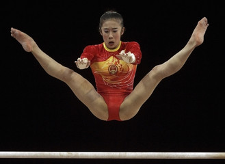 Han Bing of China competes in the uneven bars during the gymnastics women's team event at the 15th Asian Games in Doha