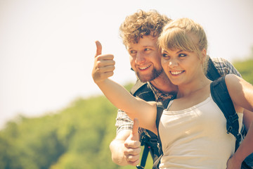 Happy tourist couple outdoor gesturing thumb up
