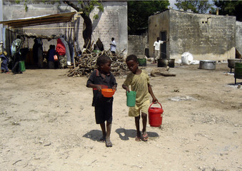 Two children carry food, which they received from a feeding centre, in the southern outskirts of Mogadishu